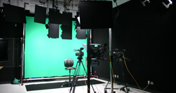 Cameras and lighting pointing at a green screen.