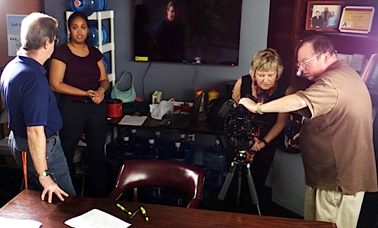 Massingill and group test video equipment in preparation for a session.