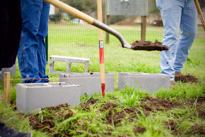 Student volunteers use shovels and cinder blocks to build planter beds in the Bearkat Community Gardens.