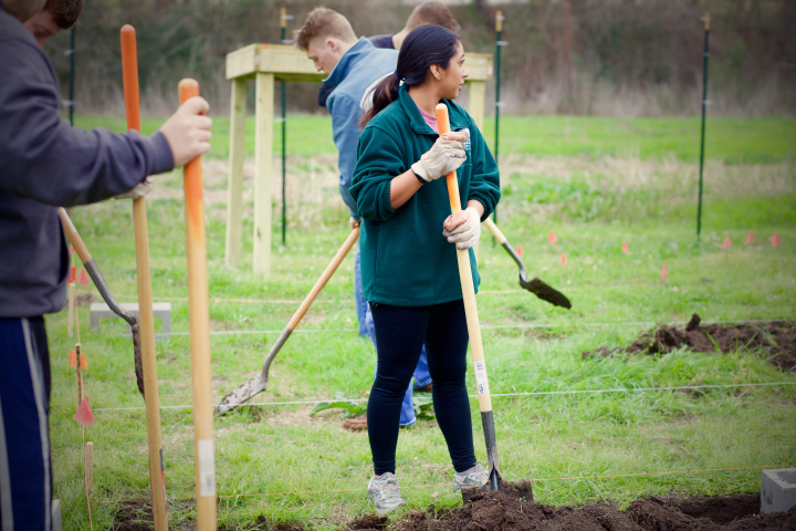 Student volunteers use shovels to dig up the ground in the Bearkat Community Gardens.