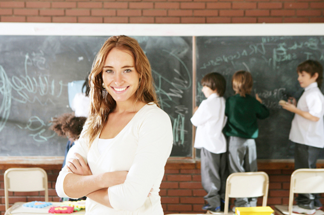 Teacher in the back of the classroom with her arms crosses as students work on the chalkboard