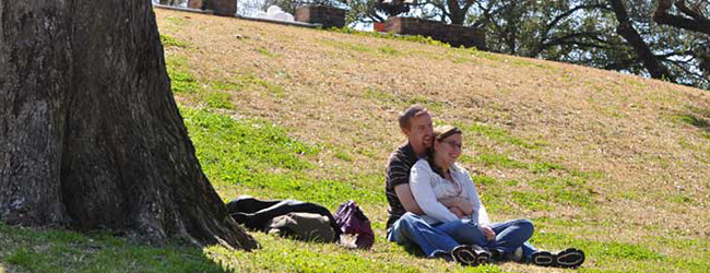 Guy Sitting in Grass with Arms around Girl