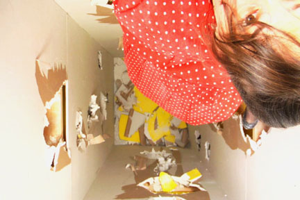 A woman crawling in a small room with cardboard and paper pieces on walls.