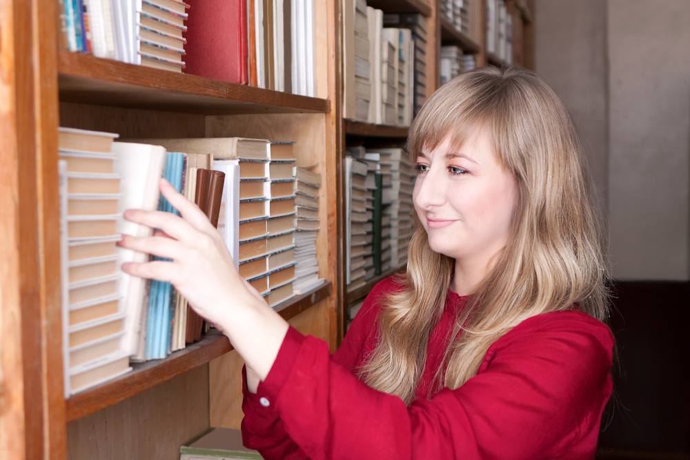 Lady in study going to books on shelve