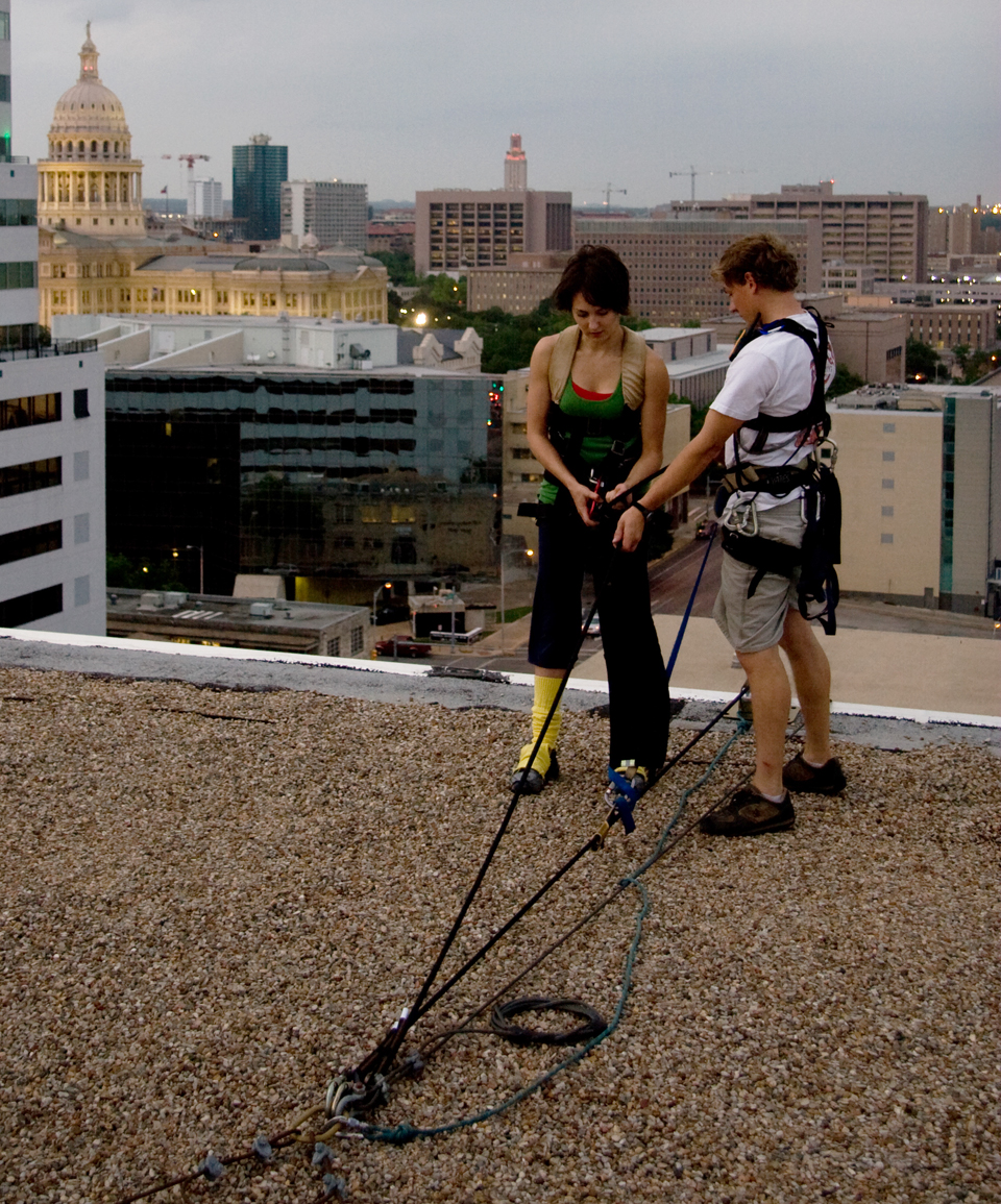 Dancers get into rigging equipment before dancing on a building