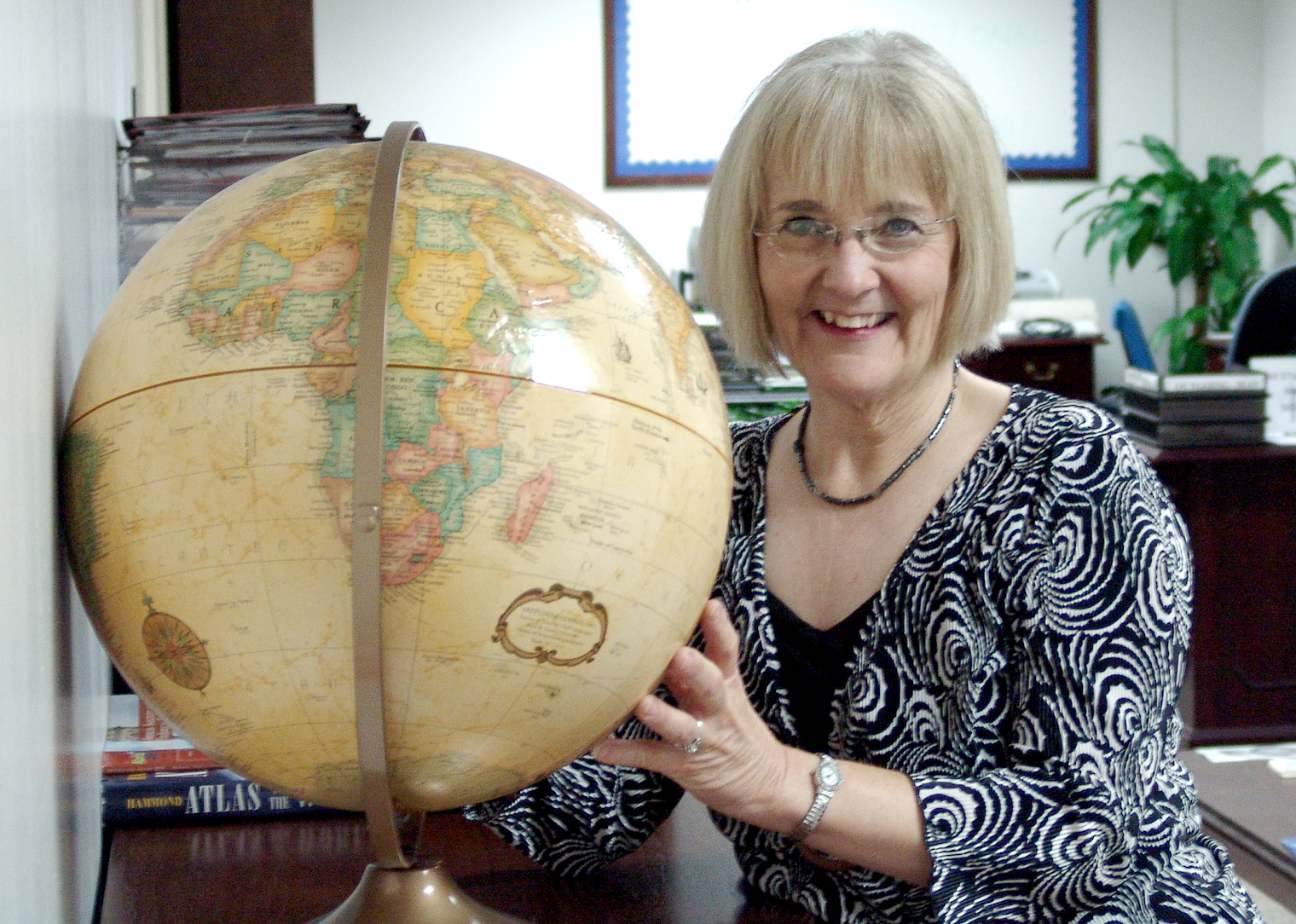 a woman smiling at a globe