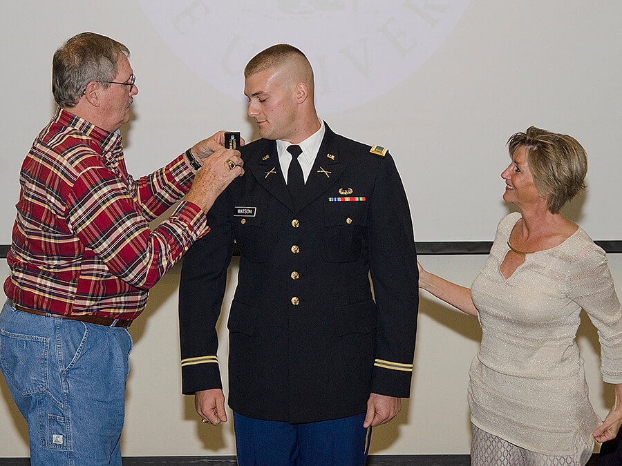 Travis Watson with his parents at his pinning ceremony.