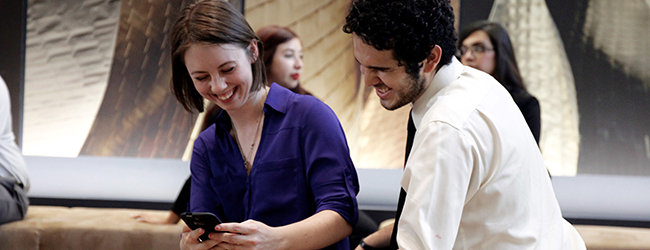 Two students look and laugh at a phone.