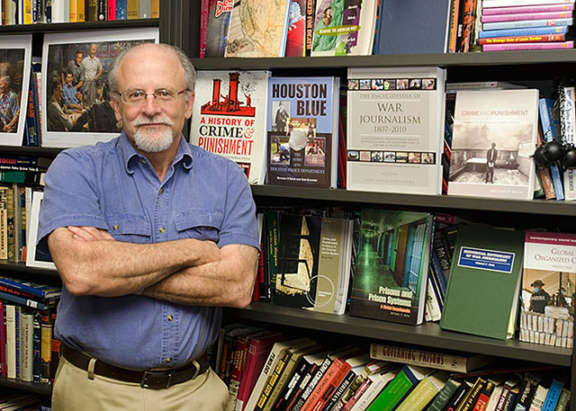 Mitchel Roth posing in front of a bookshelf featuring his book