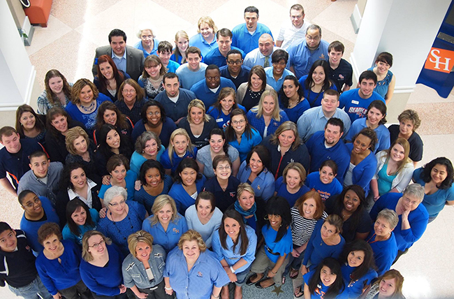group photo of participants wearing blue shirts