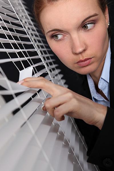 woman peeking out through window blinds