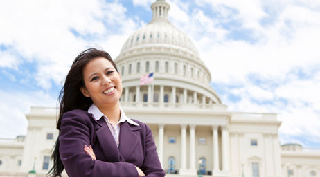 A woman stands in front of the capitol building of the United States of America.