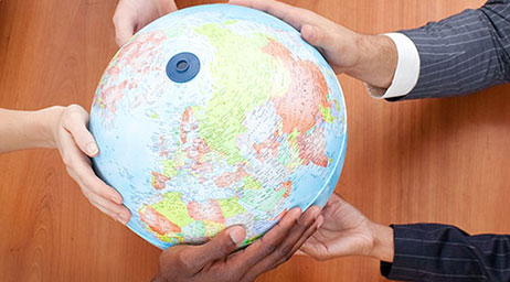 A group of students have their hands on a globe.