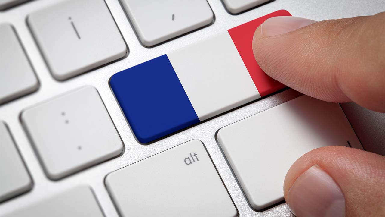 A man's fingers on a computer keyboard pressing a button colored like the French flag.