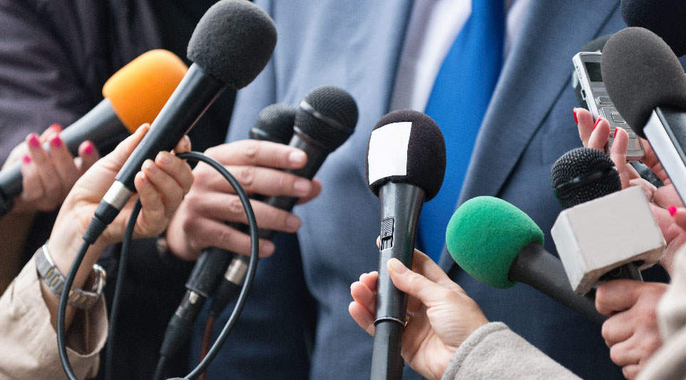 A public relations specialist speaking into multiple microphones.