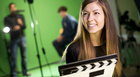 A person in front of other people using a green screen on a movie set.