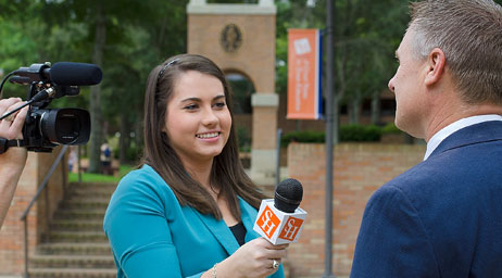 A woman is interviewing a man on camera at Sam Houston State University.