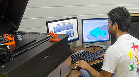 A student is using 3D design software on a computer.