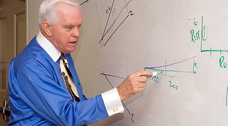 A professor at whiteboard charting an angle.