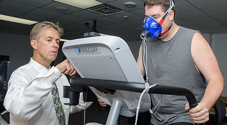 A researcher tracks a subject on a treadmill.