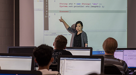An instructor is teaching a group of students code in a classroom environment.