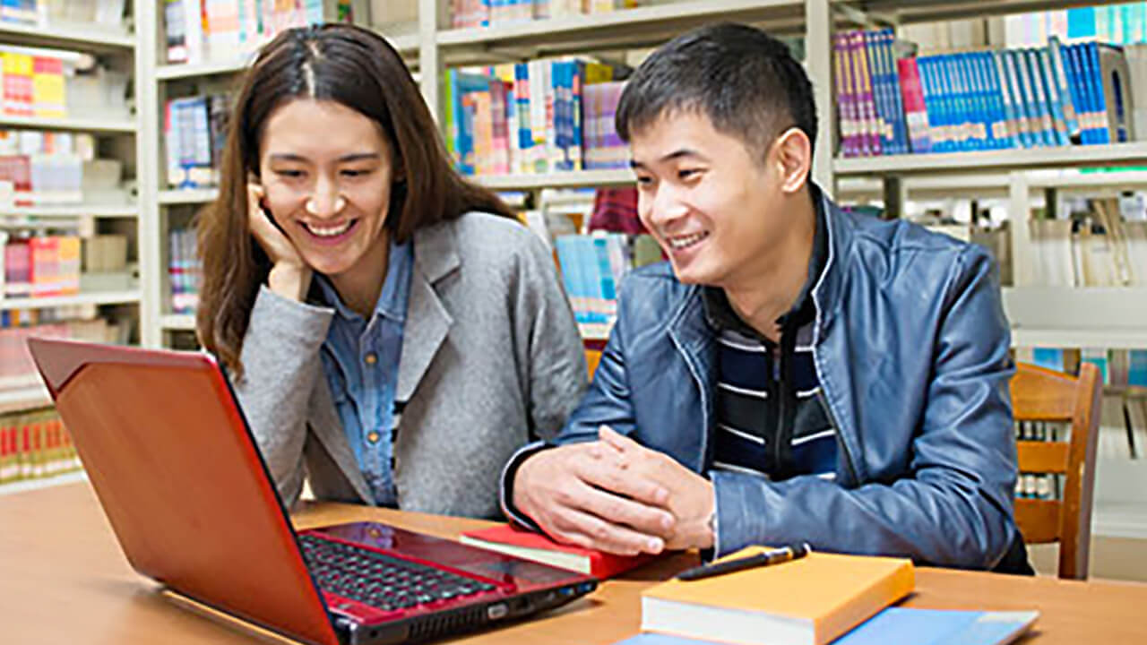 Two Students in a library looking at a laptop computer.