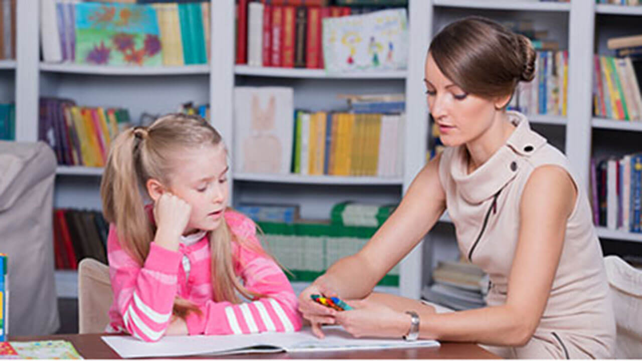 A professionally dressed female psychologist helping a young girl as they sit at a table together