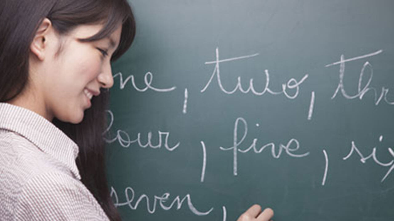 Teacher writing words on a chalboard