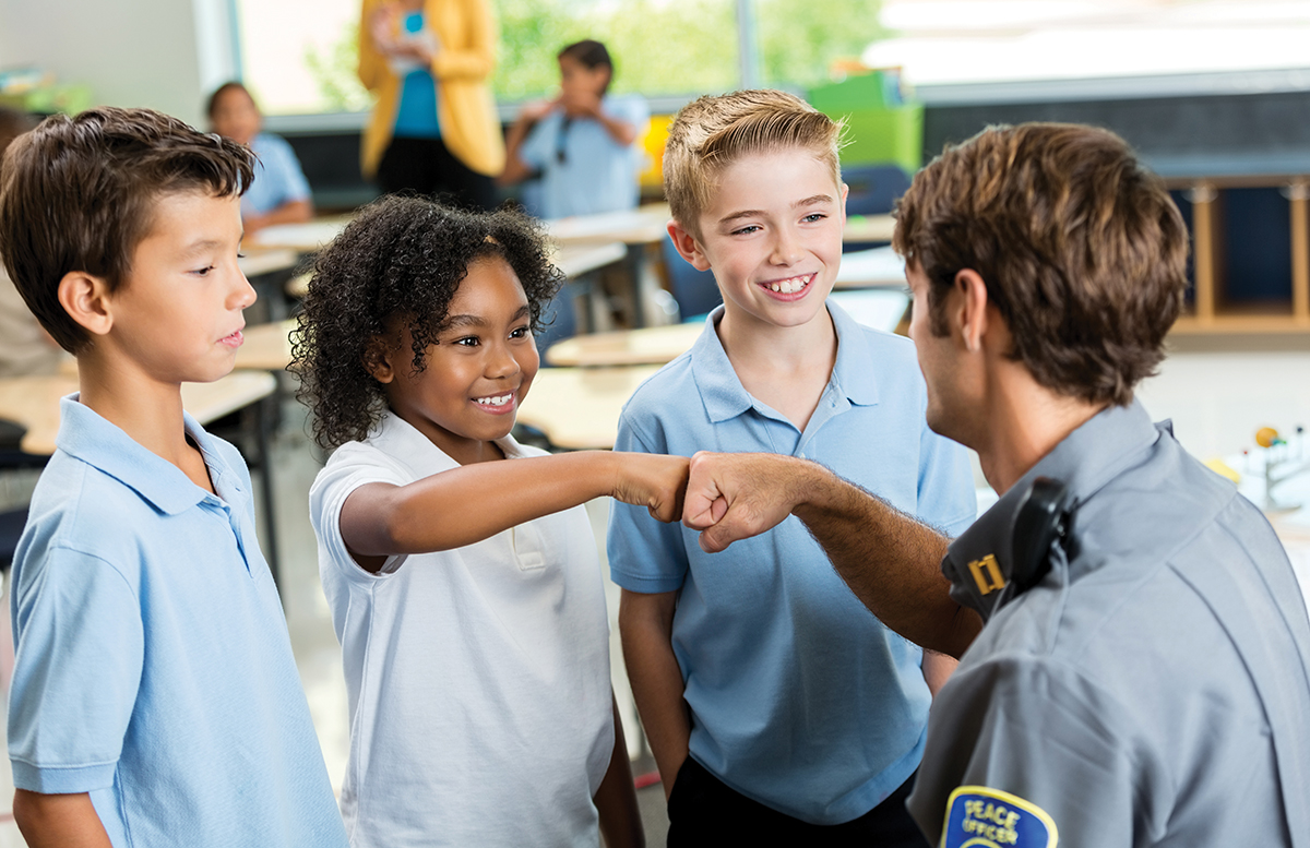 white police officer and Black child fist bump