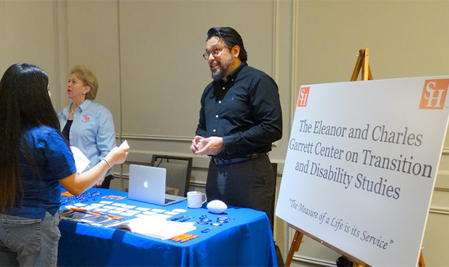 Dr. Jaime B. Durán working at an information table during a conference