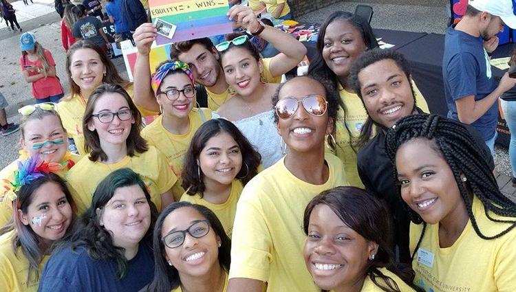 Students posing in yellow shirts with Pride Flag for LGBT History Month.
