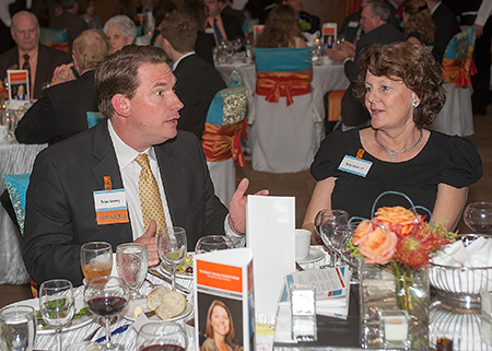 Brian Sweany talking with others at his table during dinner
