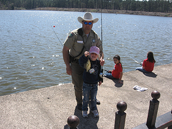 Ingram posing with children fishing